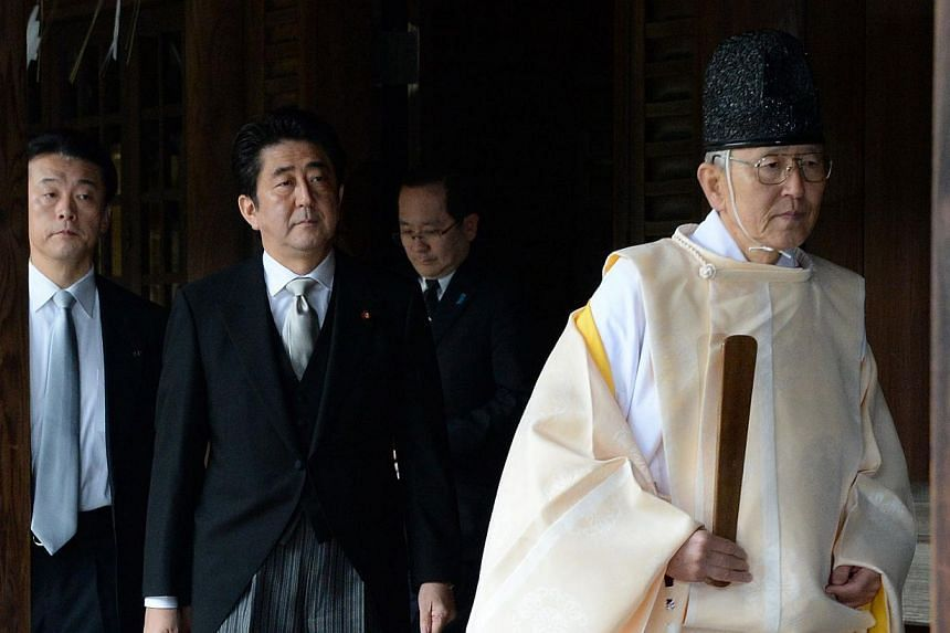 """A Shinto priest (right) leads Japanese Prime Minister Shinzo Abe (centre) as he visits the controversial Yasukuni war shrine in Tokyo on Dec 26, 2013, in a move Beijing condemned as """"absolutely unacceptable"""".China said on Monday, Dec 30, 2013,"""