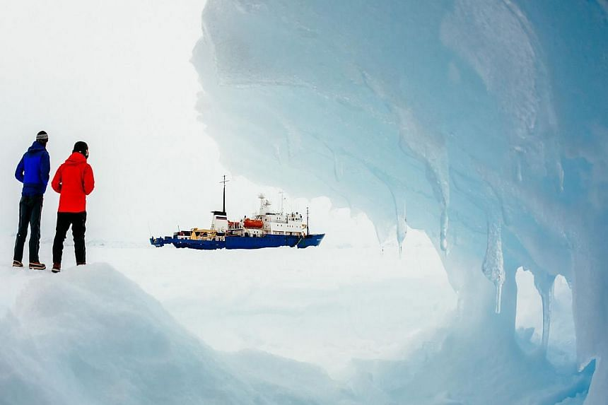 This image taken by passenger Andrew Peacock of www.footloosefotography.com on Dec 30, 2013, shows the ship MV Akademik Shokalskiy (centre) still stuck in the ice off East Antarctica, as it waits to be rescued. Severe Antarctic weather was slowing an
