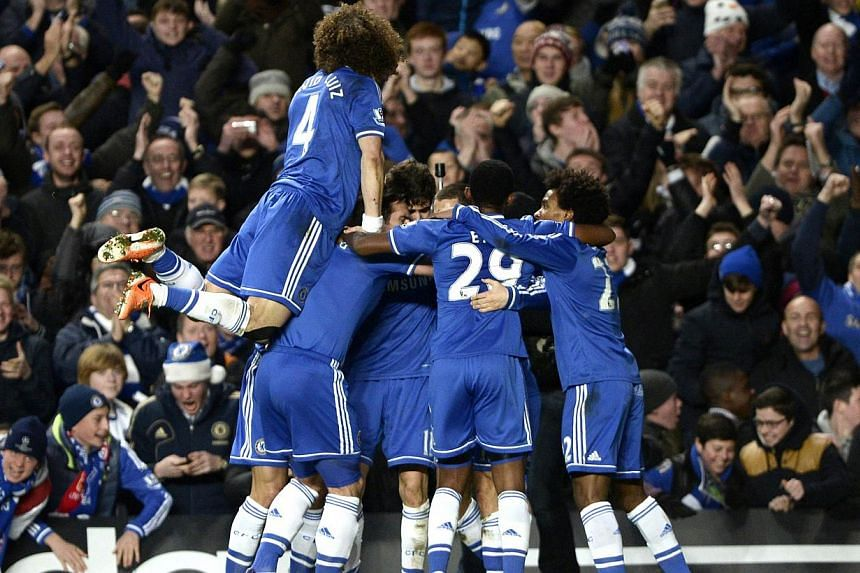 Chelsea players celebrate after Eden Hazard (obscured) scored a goal against Liverpool during their English Premier League soccer match at Stamford Bridge in London on Dec 29, 2013. -- PHOTO: REUTERS
