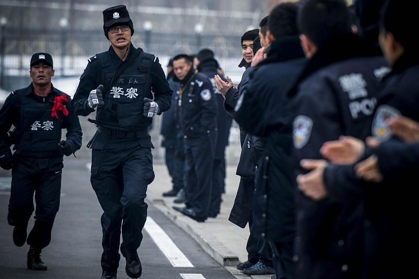 """A file photo shows two SWAT policemen (left) running while taking part in a competition during their winter training session in Urumqi, northwest China's Xinjiang region. Eight """"attackers"""" armed with knives and explosives were killed on December 30 d"""