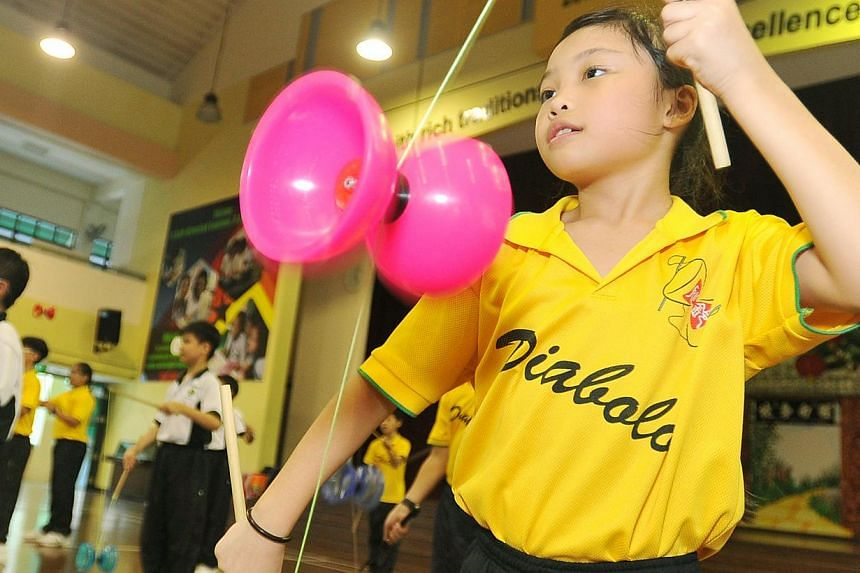 Pupils at Xingnan Primary School performing on the diabolo, a traditional Chinese game. Research has found that CCAs enhance educational outcomes up to a point, especially if sustained over time.