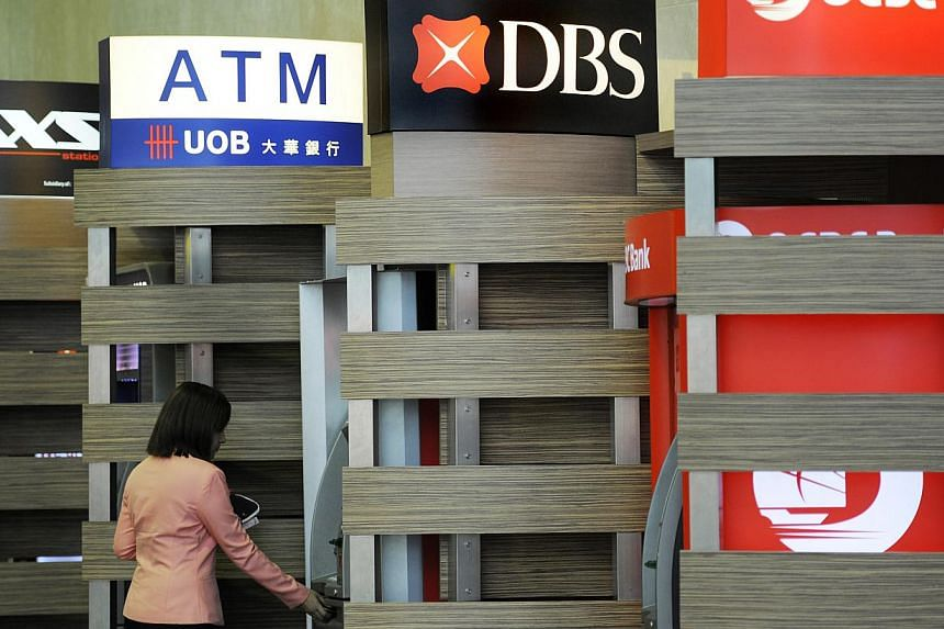 A customer uses a DBS Group Holdings Ltd automated teller machine (ATM) at Changi Airport in Singapore on Thursday, July 28, 2011. Businesses continued to borrow more money at a faster pace from banks in November, according to preliminary d