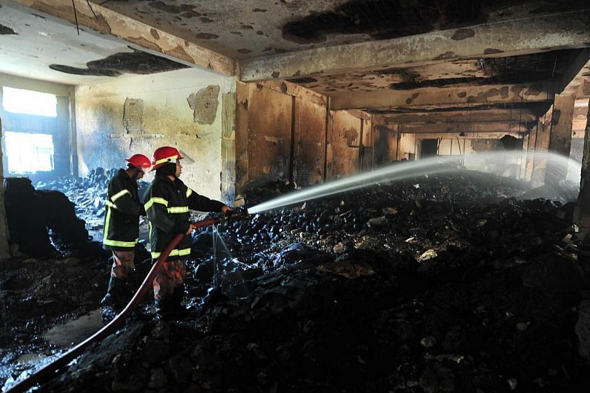 Bangladeshi firemen extinguish a fire in the nine-storey Tazreen Fashion plant in Savar, about 30km north of Dhaka on Nov 25, 2012. A Bangladesh court on Tuesday, Dec 31, 2013, ordered the arrest of the owners and four others over the country's