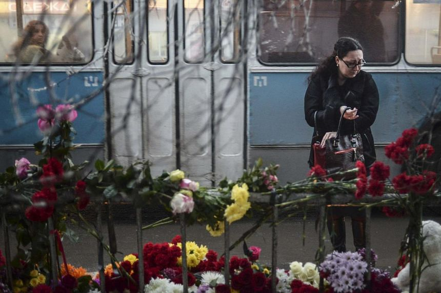 A woman reacts while standing near flowers placed at the site of an explosion on a trolleybus in Volgograd on Tuesday, Dec 31, 2013. Russia beefed up security and mourned its dead on Tuesday as the toll from jarring successive-day suicide strike