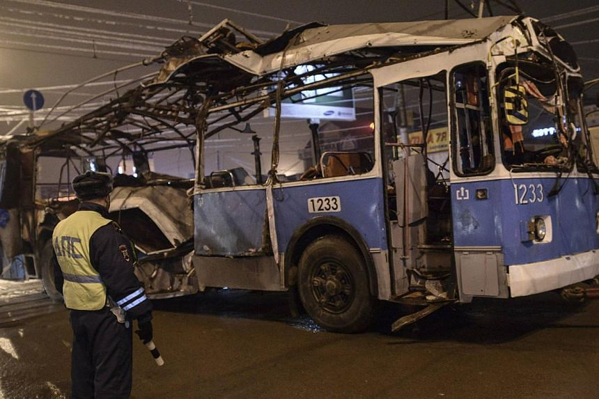 A policeman watches as a bus, destroyed in an earlier explosion, is towed away in Volgograd on Monday, Dec 30, 2013. Police detained dozens of people on Tuesday, Dec 31, 2013, in sweeps through the Russian city of Volgograd after two deadly atta