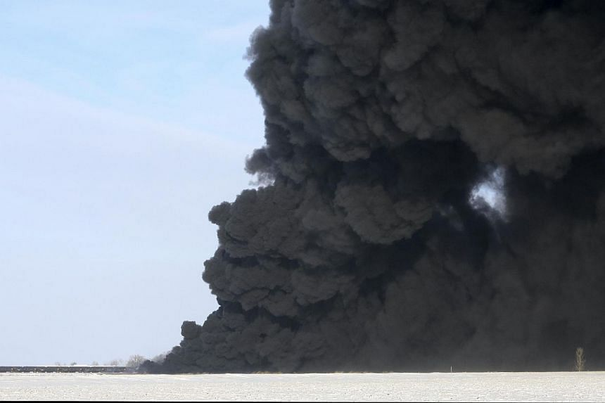 A plume of smoke rises from scene of a derailed train near Casselton, North Dakota on Dec 30, 2013.A train carrying crude oil in North Dakota collided with another train on Monday, setting off a series of explosions that left at least 10 cars a