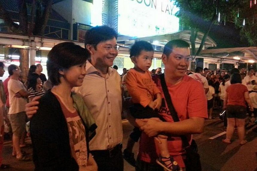 West Coast GRC MP Lawrence Wong, who is also Acting Minister for Culture, Community and Youth and Senior Minister of State for Communications and Information, pose with residents at a countdown party at Boon Lay Place. -- ST PHOTO: AUDREY TAN
