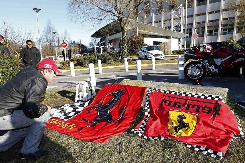 Dario, a Ferrari local fan, displays flags in front of the entrance of the emergency services at the CHU Nord hospital in Grenoble, French Alps, where retired seven-times Formula One world champion Michael Schumacher is hospitalised after a ski accid