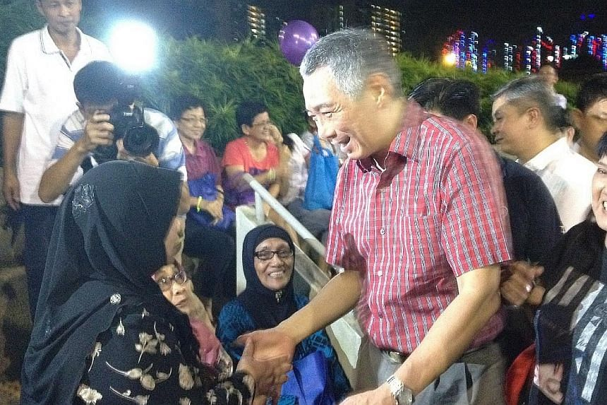 Prime Minister Lee Hsien Loong shaking hands with residents at a countdown party in Ang Mo Kio, Dec 31, 2013. -- ST PHOTO: CHARISSA YONG