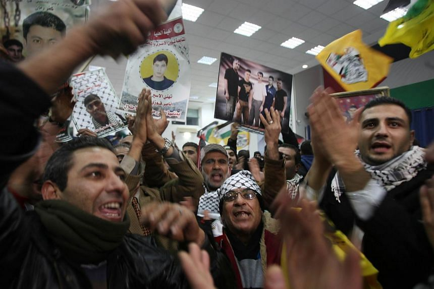 Friends and family members of the 26 Palestinian prisoners who are expected to be released on Dec 30, 2013 celebrate their imminent release from Israeli jail in the West Bank city of Ramallah.Israel released the 26 Palestinian prisoners early o