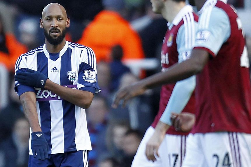 "West Bromwich Albion's French striker Nicolas Anelka celebrating his goal with the contentious ""quenelle"" salute during the English Premier League football match between West Ham United and West Bromwich Albion at The Boleyn Ground, Upton Park in eas"