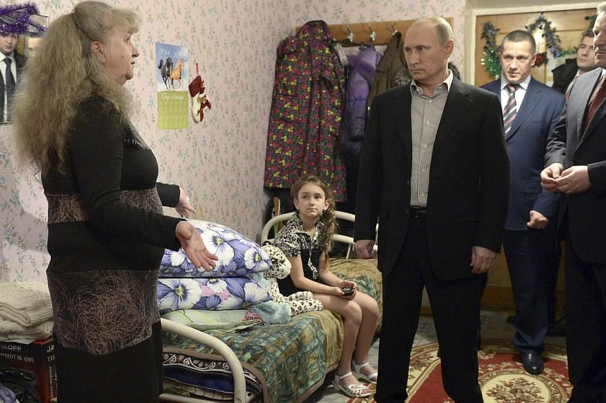 """Russian President Vladimir Putin (centre) visits residents of temporary housing for flood victims in the far eastern city of Khabarovsk, on Dec 31, 2013. Russian President Vladimir Putin on Tuesday, Dec 31, 2013, vowed to annihilate """"terrorists"""" foll"""