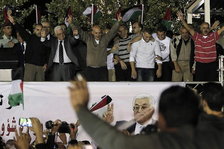 Palestinian President Mahmoud Abbas (second left) welcomes Palestinian prisoners released from Israeli prisons in the West Bank city of Ramallah early on Oct 30, 2013. The United States on Monday welcomed Israel's expected release of 26 Palestin