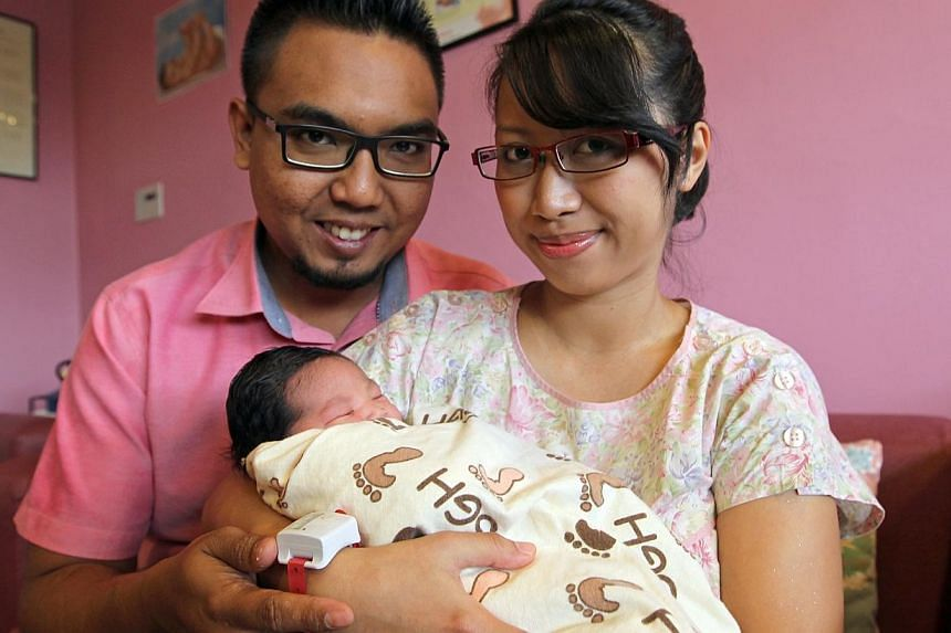 The first-born daughter of (right) Nur Asilah bte Al, 25, and Iswardy bin Ithnain, 27, was born at 12:01:00 am, Jan 1, 2014, on New Year's Day at Singapore General Hospital.-- ST PHOTO:SEAH KWANG PENG