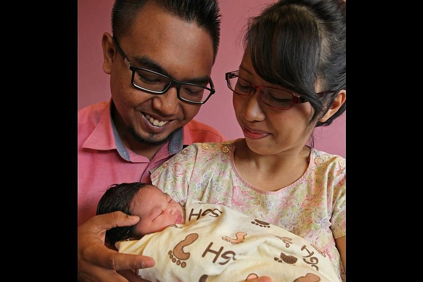 The first-born daughter of (right) Nur Asilah bte Al, 25, and Iswardy bin Ithnain, 27, was born at 12:01:00 am, Jan 1, 2014,on New Year's Day at Singapore General Hospital.-- ST PHOTO:SEAH KWANG PENG