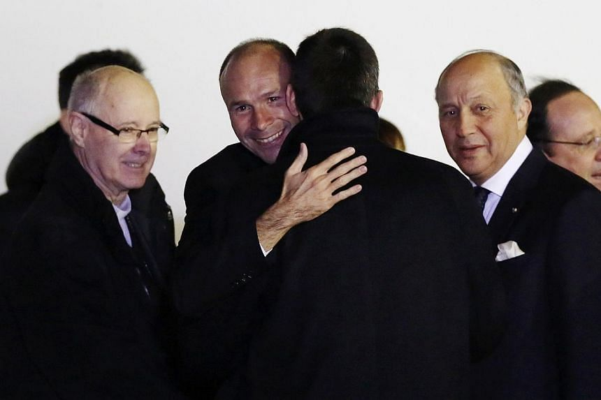 Ex-hostage and French Catholic priest Georges Vandenbeusch (second from left) embraces a family member as Monsignor Gerard Daucourt (left), Bishop of Nanterre, French Foreign Affairs Minister Laurent Fabius (second from right) and French President Fr