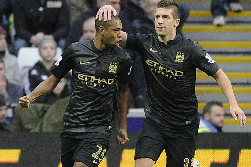 Manchester City's Fernandinho (left), celebrates scoring a goal against Swansea City with Matija Nastasic during their English Premier League soccer match at the Liberty Stadium in Swansea, Wales, on Jan 1, 2014.Manchester City start the new ye