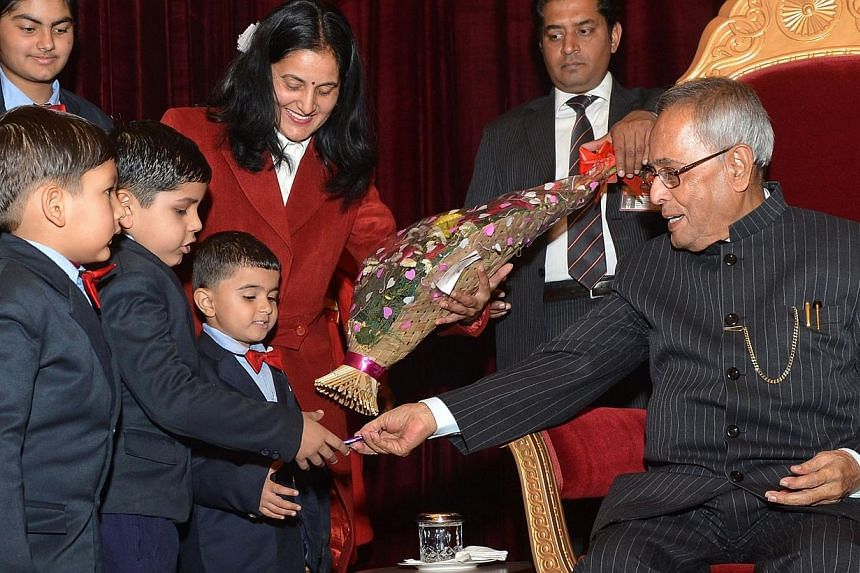 Indian President Pranab Mukherjee interacts with schoolchildren during New Year's celebrations in New Delhi, on Jan 1, 2014. Mukherjee took the final step to create a powerful anti-graft watchdog on Wednesday, signing it into law two years after