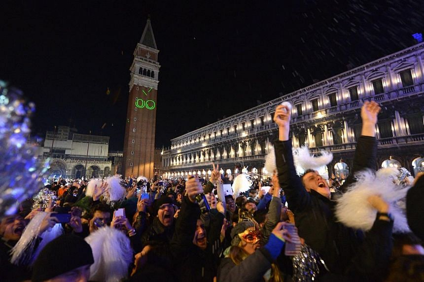 People gather to celebrate the New Year at the Piazza San Marco in Venice, early on Jan 1, 2014. The toll from exploding fireworks in Italy fell sharply this New Year following a stepped-up public information campaign, with revellers from Milan