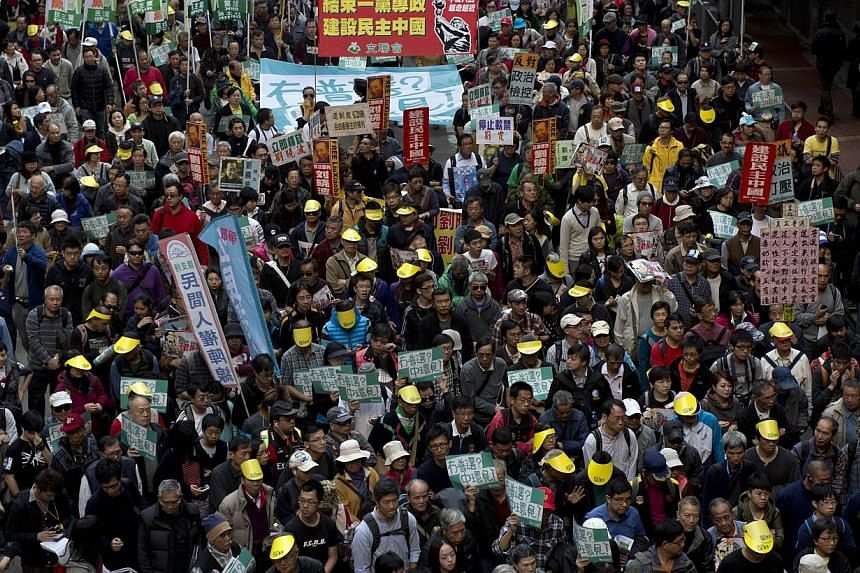 Protesters march along a street in Hong Kong during a pro-democracy demonstration on Jan 1, 2014. -- PHOTO: AFP