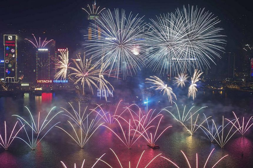 Fireworks explode over Victoria Harbour and Hong Kong Convention and Exhibition Centre during a pyrotechnic show to celebrate the New Year in Hong Kong on Jan 1, 2014. -- PHOTO: REUTERS