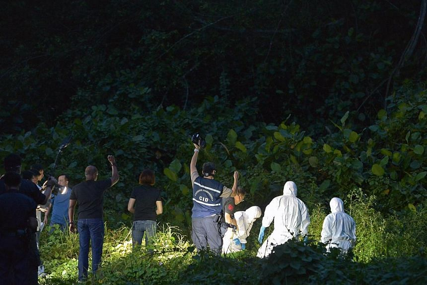 Investigators don suits to extricate the body from a ditch.-- ST PHOTO:KUA CHEE SIONG