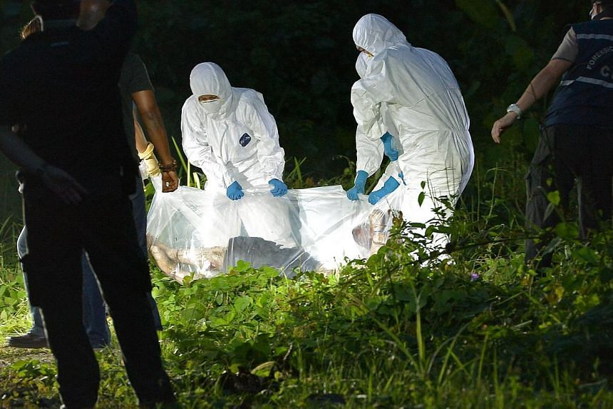 Investigators lifting the body into a clearing.-- ST PHOTO:KUA CHEE SIONG