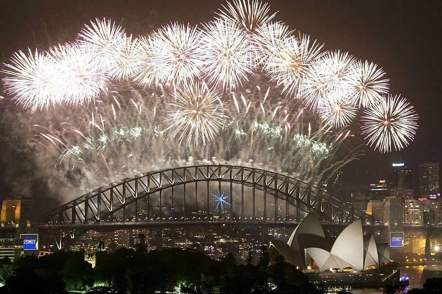 Fireworks explode over Sydney Harbour at midnight, ushering in the new year, in Sydney, on Jan 1, 2014. -- PHOTO: REUTERS
