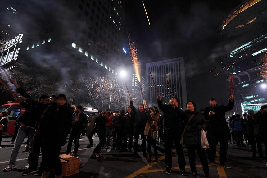 Thousands of people celebrate the New Year during a countdown event in front of the Bosingak Pavilion, in downtown Seoul, South Korea, on Jan 1, 2014. -- PHOTO: AFP