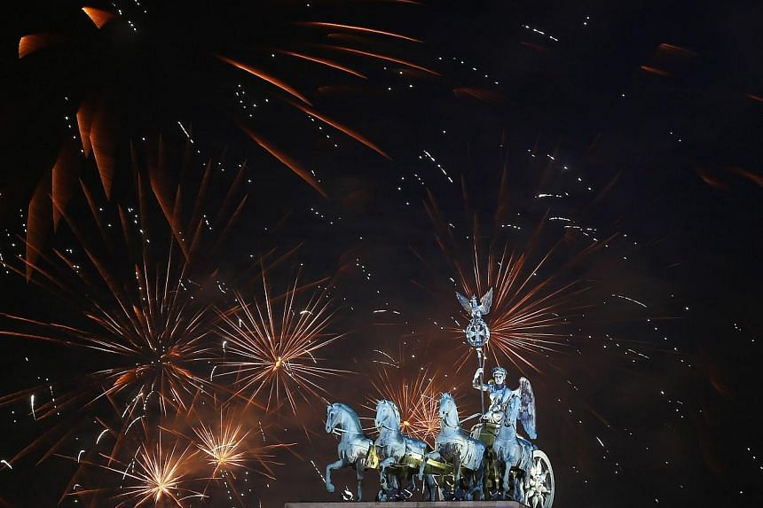 Fireworks explode next to the Quadriga sculpture atop the Brandenburg gate during New Year celebrations in Berlin, on Jan 1, 2014. -- PHOTO: REUTERS