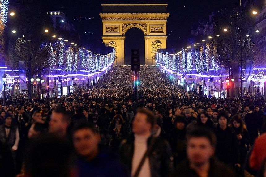 People celebrate the New Year on the Champs-Elysees in Paris, on Jan 1, 2014. -- PHOTO: AFP