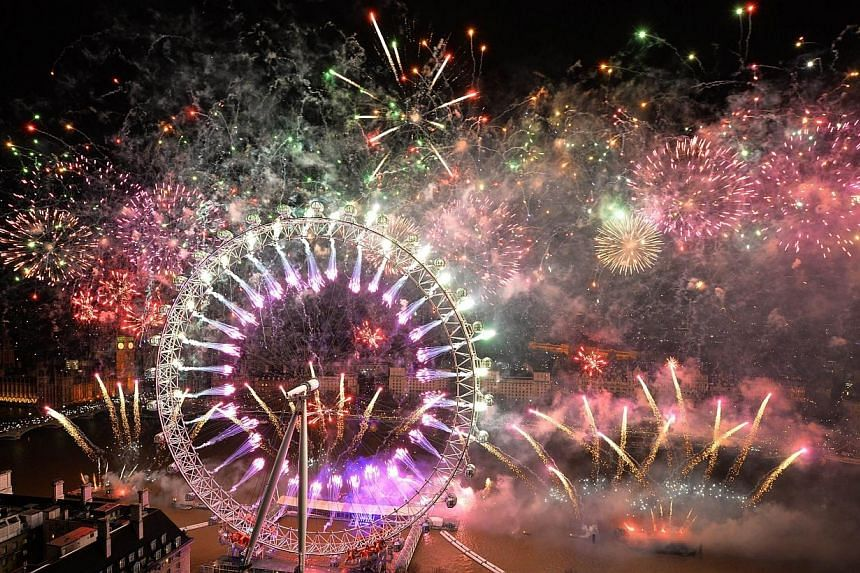 Fireworks explode over the London Eye and the Houses of Parliament along the river Thames during the New Year celebrations in central London just after midnight, on Jan 1, 2014. -- PHOTO: AFP