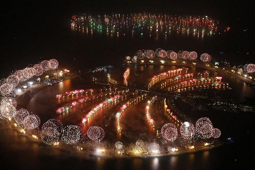 Fireworks explode over Palm Jumeirah in Dubai, on Jan 1, 2014, to celebrate the new year. Dubai shattered the world record for the largest ever pyrotechnic display on New Year's Eve with a show involving more than half a million fireworks, Guinness W