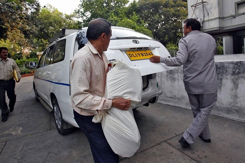Central Bureau of Investigation (CBI) officials carry a bag of documents after conducting a raid at a building as part of probes into the AgustaWestland bribery case in New Delhi, on March 13, 2013.India has cancelled a US$770 million (S$972 mi