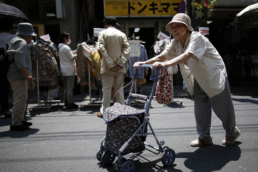 An elderly woman walks past on a street at Tokyo's Sugamo district in Tokyo, on June 4, 2013.Japan's population fell by a record 244,000 in 2013, according to health ministry estimates released on Wednesday, Jan 1, 2014, highlighting concerns o