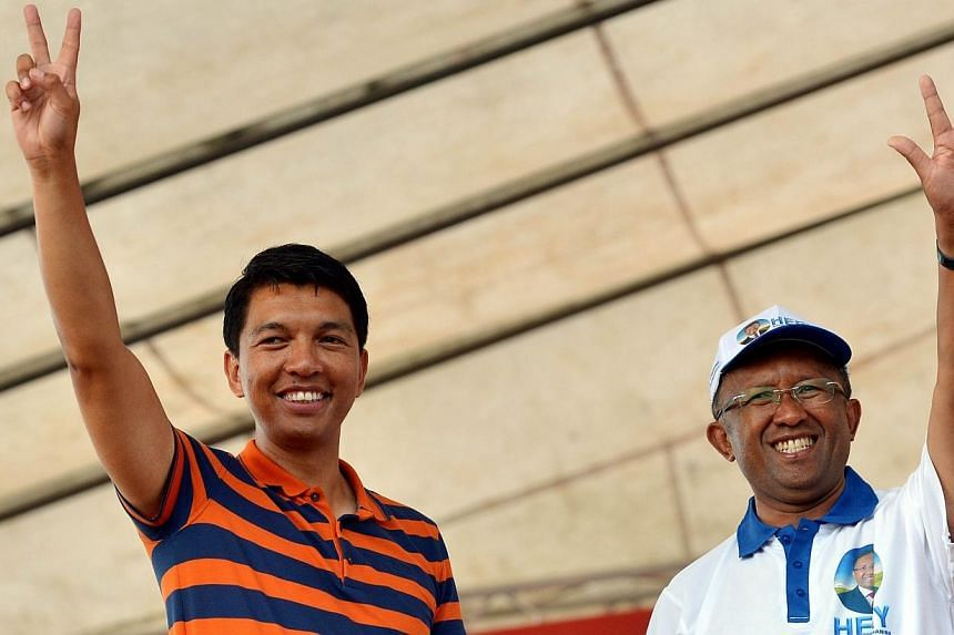 Presidential candidate Hery Rajaonarimampianina (right) of Hery Vaovao ho an'i Madagasikara party and Madagascar strongman Andry Rajoelina flashing the party's sign during a rally ahead of the upcoming presidential election, on Dec 20, 2013.The