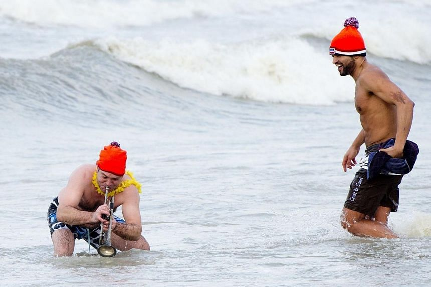 Two men take part in the traditional sea bathing to mark the start of the new year, on Jan 1, 2014, in Scheveningen.Tens of thousands of revellers across the Netherlands braved the chilly winter weather on Wednesday, Jan 1, 2014, to take a trad