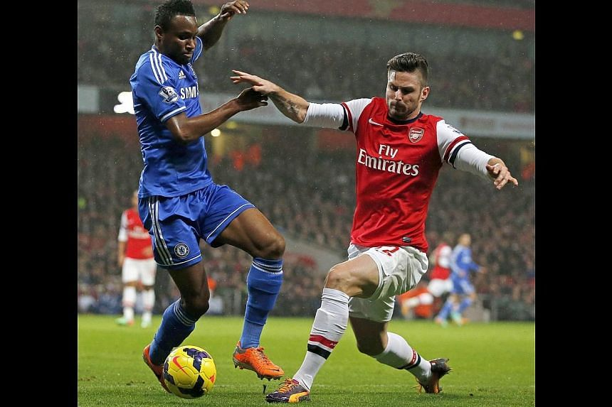 Arsenal's French striker Olivier Giroud (right) vies with Chelsea's Nigerian midfielder John Mikel Obi during the English Premier League football match between Arsenal and Chelsea at the Emirates Stadium in London, on Dec 23, 2013. Arsenal manager Ar