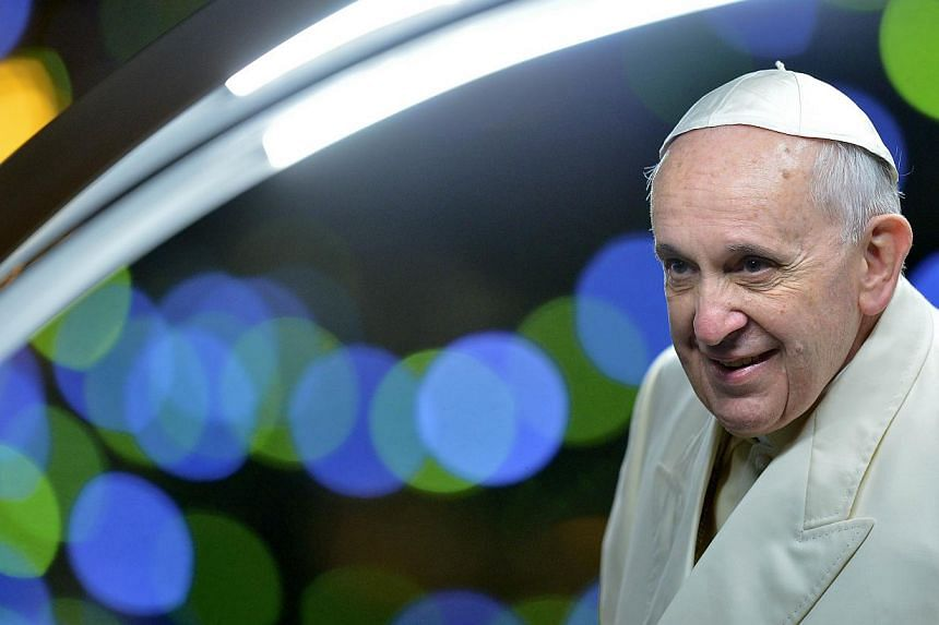 Pope Francis smiles to the faithful after visiting the cribb in St Peter's square at the Vatican on Dec 31, 2013. Pope Francis urged the people of Rome not to let the beauty of their city to blind them to the growing number of homeless, refugees, and