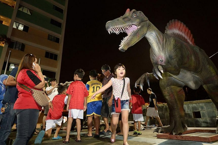 Children interact with robot dinosaurs at Boon Lay town's countdown party on Dec 31, 2013. -- ST PHOTO: NG SOR LUAN