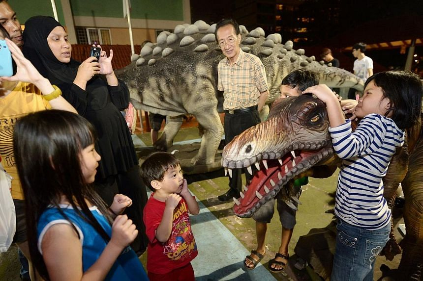 Children interact with robot dinosaurs atBoon Lay town's countdownparty on Dec 31, 2013.-- ST PHOTO:NG SOR LUAN