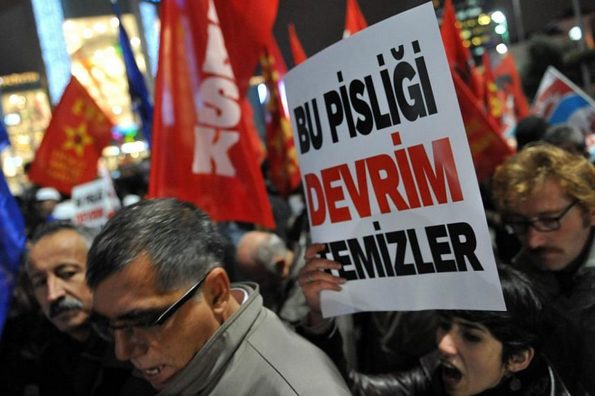 """A Turkish protester holds up a placard reading """"Only revolution can clear this corruption"""" during a demonstration against goverment on Dec 30, 2013 in Istanbul. Hundreds of demonstrators flooded metro stations in Turkey on Tuesday in fresh protests a"""