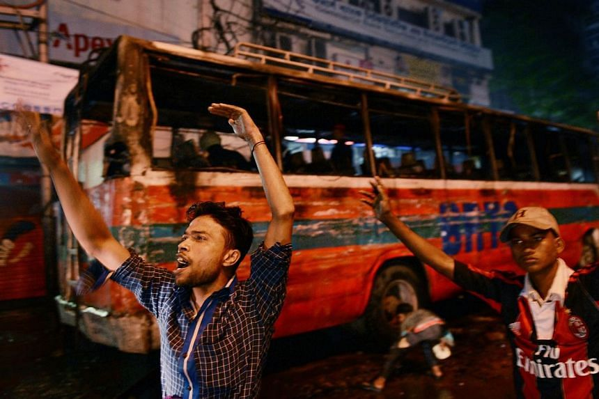 A Bangladeshi resident tries to keep traffic away from a smoldering bus after it was set on fire in Dhaka on Jan 2, 2014. Bangladesh's Prime Minister Sheikh Hasina ruled out on Thursday any last-minute cancellation of weekend elections that have been