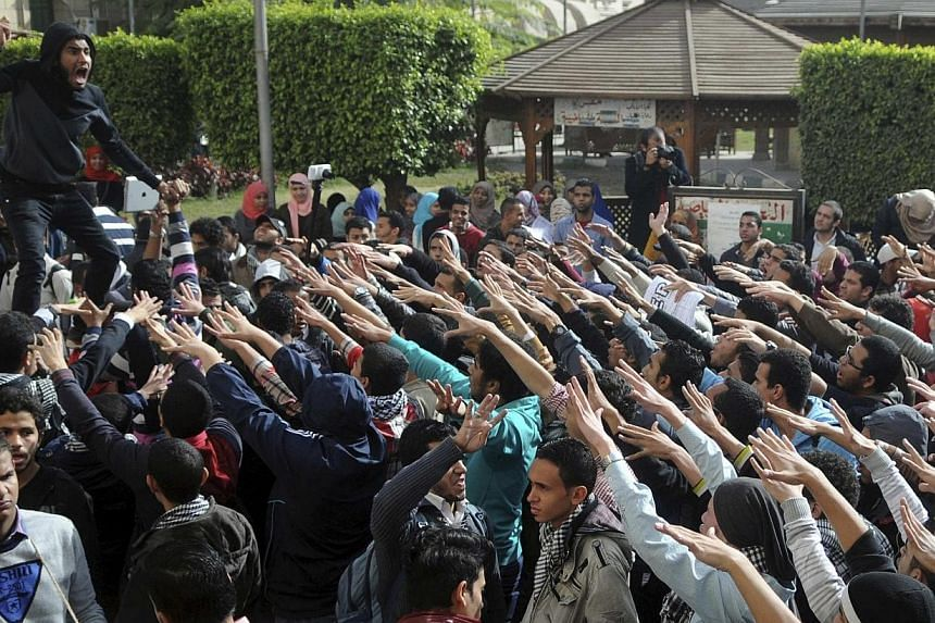 Cairo University students supporting the Muslim Brotherhood and deposed President Mohamed Morsi shout slogans at the university's campus in Cairo on Dec 29, 2013.Egypt's deposed president Mohamed Morsi and 130 others, including Hamas members, w