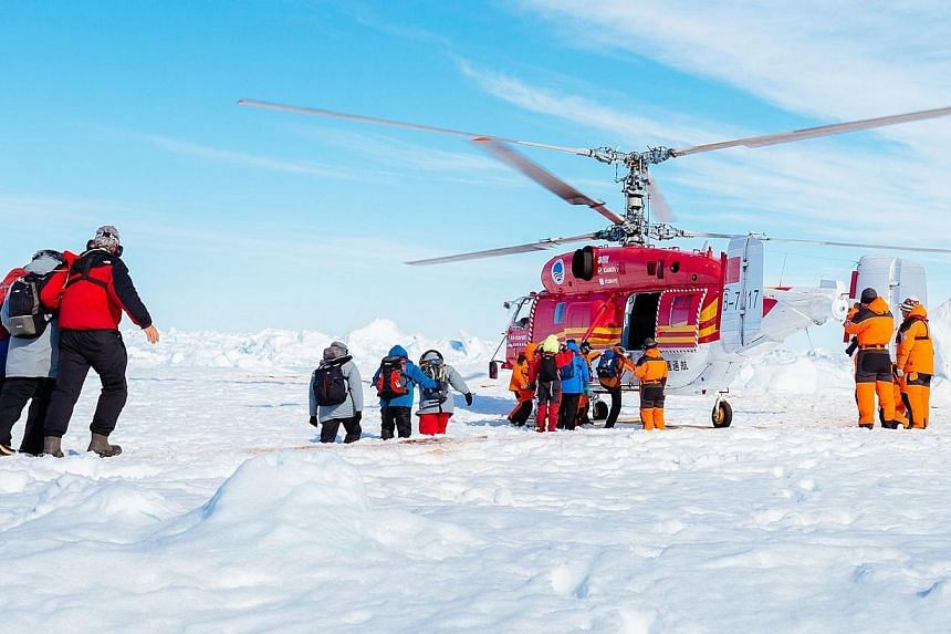 A helicopter from the nearby Chinese icebreaker Xue Long picking up the first batch of passengers from the stranded Russian ship MV Akademik Shokalskiy, on Jan 2, 2014, as rescue operations take place after over a week of being trapped in the ice off