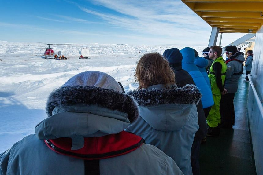 Passengers on board the stranded Russian ship MV Akademik Shokalskiy, on Jan 2, 2014, watching as a helicopter from the nearby Chinese icebreaker Xue Long picks up the first batches of passengers, as rescue operations take place after over a week of