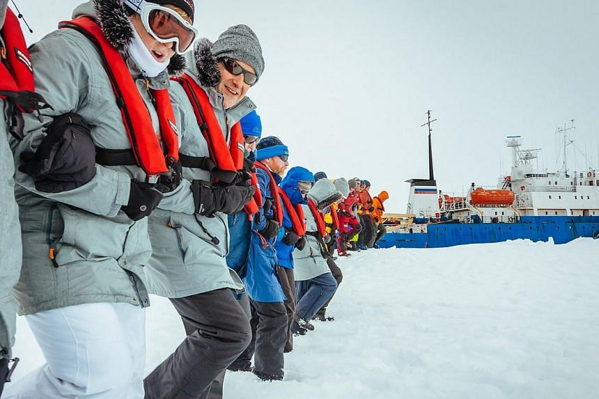 Passengers linking arms and stamping out a helicopter landing site on the ice near the MV Akademik Shokalskiy (back right), on Jan 2, 2014, still stuck in the ice off eastern Antarctica, as the ship waits for a possible helicopter rescue. -- PHO