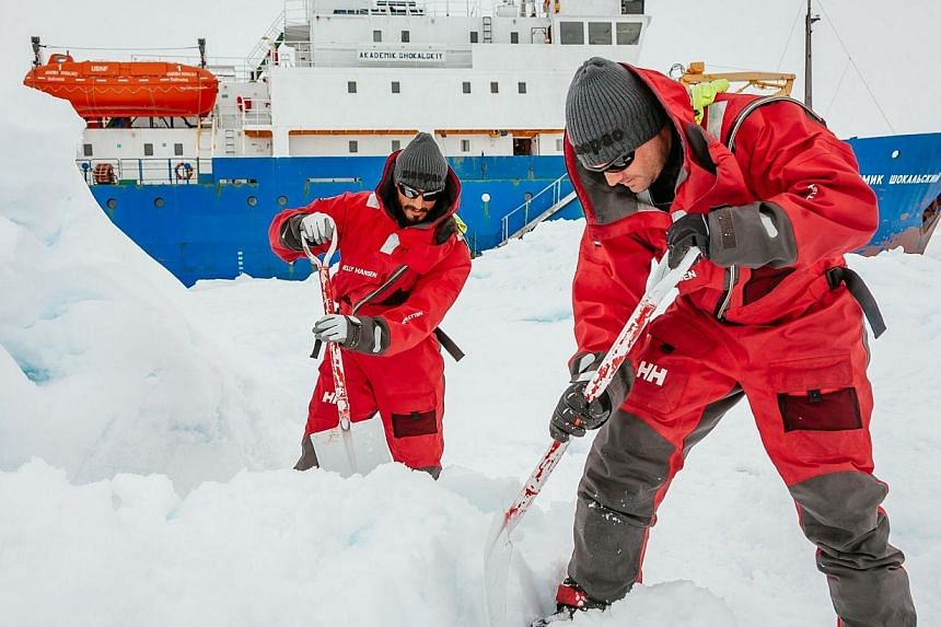Scientists from the University of New South Wales in Australia Ziggy Marzinellia and Graeme Clark preparing a suitable surface for a helicopter landing next to the MV Akademik Shokalskiy (background), still stuck in the ice off east Antarctica, on Ja