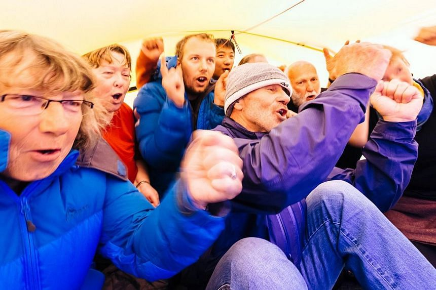 Passengers stranded on the MV Akademik Shokalskiy, still stuck in the ice off eastern Antarctica, sheltering in a tent lashed to the ships top deck as they sing a song they wrote streaming live on the Internet to mark in the new year, on Jan 2, 2014.