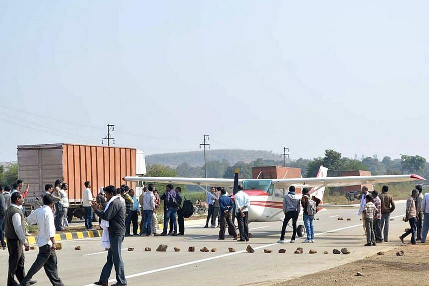 Indian officials and bystanders gather around a light aircraft after it landed on a public highway in Betul, some 50km south of Bhopal in the central Indian state of Madhya Pradesh, on Dec 31, 2013.A wealthy businessman who landed his private p